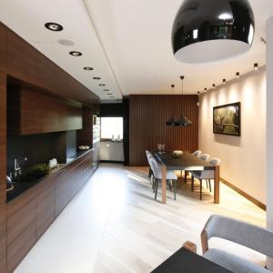 W tej nowoczesnej jadalni połączonej z kuchnią, nad stołem górują nowoczesne czarne lampy. Projekt: Jan Sikora. Fot. Bartosz Jarosz