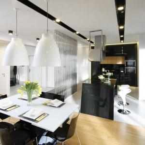 Białe minimalistyczne wnętrze uzupełniają białe, pokaźnych rozmiarów, lampy na stołem. Projekt: Monika i Adam Bronikowscy. Fot. Bartosz Jarosz