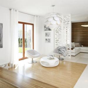 Drewno dominuje w zacisznej części salonu, ukrytego za delikatnymi ażurowymi panelami. Projekt: Agnieszka Ludwinowska. Fot. Bartosz Jarosz