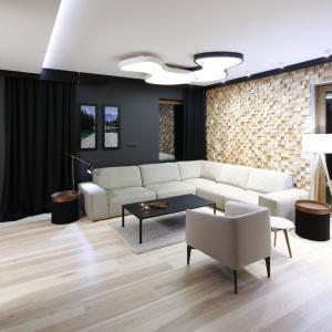 Na uwagę zasługuje ściana za kanapą, którą wykonano z ponad tysiąca ręcznie przygotowanych elementów drewna. Tworzą one niezwykłą mozaikę. Projekt: Jan Sikora, Fot. Bartosz Jarosz