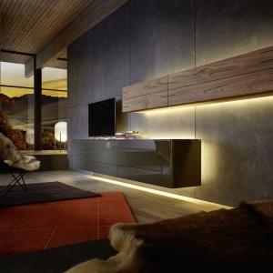 Niskie, podwieszane regały i moduły z kolekcji GENTIS o minimalistycznej formie, którym lekkości dodaje podświetlenie. Fot. Hülsta
