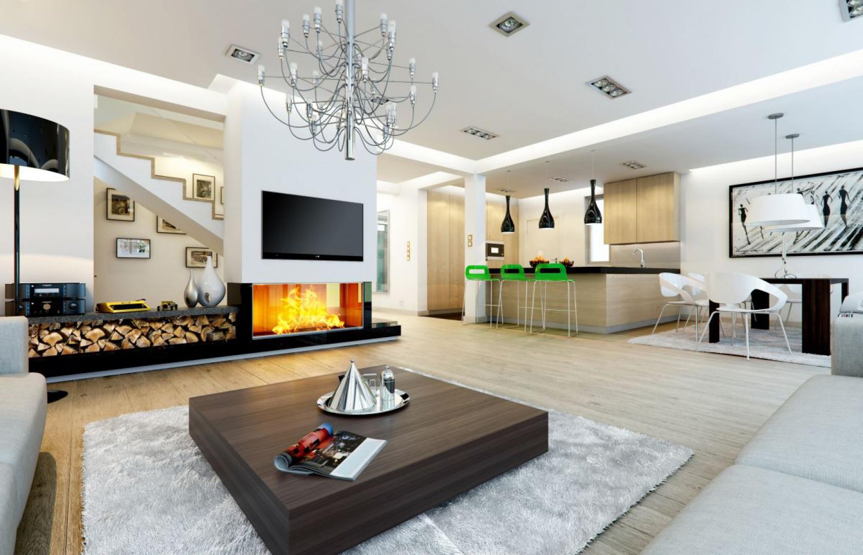 """Centralnie usytuowany kominek i kącik TV oraz """"otwarcie"""" perspektywy na schody pozwala wyeksponować każdy element wystroju wnętrza domu. Fot. MG Projekt"""
