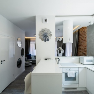 Przestrzeń na kuchnię wygospodarowano tuż przy salonie. Tu również wykorzystano biel. Projekt: Nowa Papiernia. Fot. Maciej Lulko