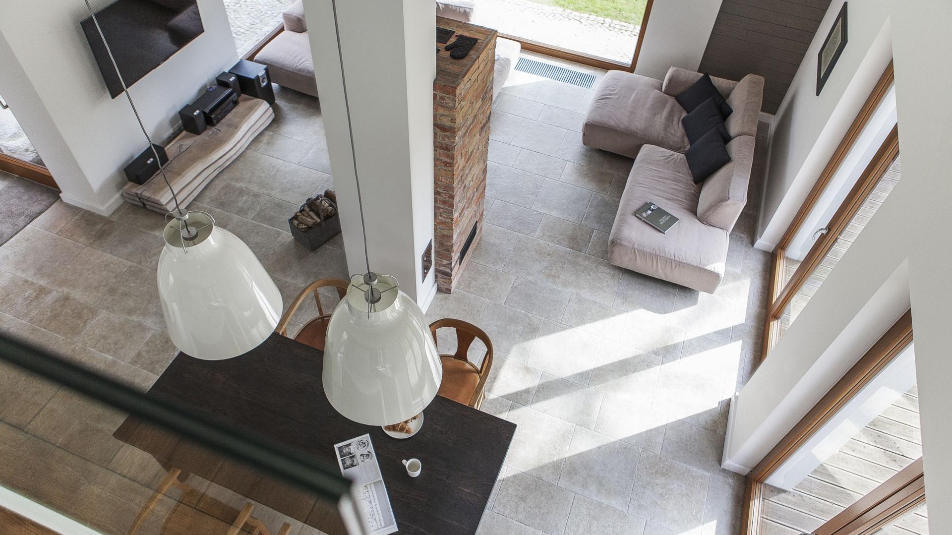 Salon o wysokości dwóch kondygnacji potęguje wrażenie przestrzeni, a liczne, wysokie okna rozjaśniają wnętrze zdając się optycznie powiększać jego metraż. Projekt: Anna Nowak-Paziewska, Pracownia MAFgroup. Fot. Emi Karpowicz