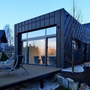 Pozostała część domu pokryta jest szczelnie czarną blachą tytanowo-cynkową. Połączenie z jasnym kamieniem jest eleganckie i ponadczasowe, pomimo że dom jest w swej formie niezywkle nowoczesny. Projekt: arch. Tadeusz Lemański. Fot. Tomasz Zakrzewski