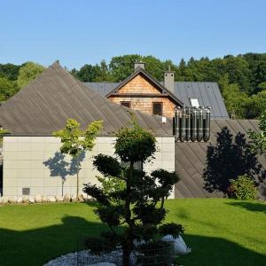 Dom, pomimo swojej nowoczesnej formy, dobrze wpisuje się w otoczenie domów jednorodzinnych z dwuspadowymi dachami. Projekt: arch. Tadeusz Lemański. Fot. Tomasz Zakrzewski