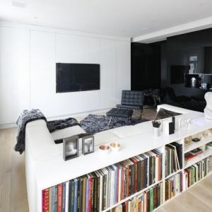 Biały regał kolorystycznie zlewa się z nowoczesną białą kanapą. Różnobarwne grzbiety książek dodają temu wnętrzu kolorystycznych akcentów. Projekt: Małgorzata Muc, Joanna Scott . Fot. Bartosz Jarosz