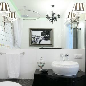 Nietypowa mozaika, imitująca pikowaną tkaninę idealnie wpisuje się w charakter łazienki urządzonej w stylu retro. Wyjątkową ozdobnie potraktowano tu ścianę z lustrem - niesamowicie prezentują się tu kinkiety. Projekt: Małgorzata Galewska. Fot. Bartosz Jarosz