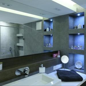 W tej szarej łazience, wykończonej betonem, doskonale sprawdza się jednolita lustrzana tafla. Projekt: Agnieszka Hajdas-Obajtek. Fot. Bartosz Jarosz