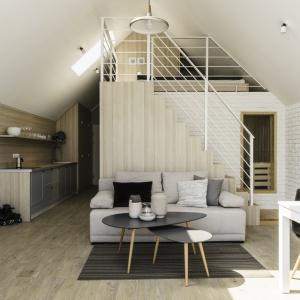 W pomieszczeniach dominuje jasne drewno, na ścianach w strefie dziennej klasyczną farbę zestawiono z białą cegłą. Projekt: Anna Maria Sokołowska. Fot. Foto&Mohito
