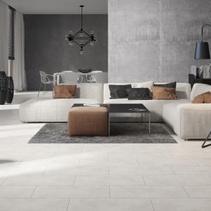 Szare płytki na podłodze w salonie idealnie komponują się z betonem na ścianie. Fot. Opoczno