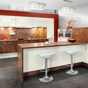 Szyk i elegancję w kuchni KAMPlus uzyskano dzięki frontom akrylowanym o niemal lustrzanym połysku w odcieniu waniliowym, które połączono znie mniej prestiżowym dekorem marmur ceramic rdzawy. Fot. KAM