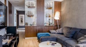 Trzypokojowe mieszkanie przy ul. Hożej w Warszawie. Dominują tu ciepłe kolory oraz naturalne dekory drewna. Charakterystycznym akcentem są dekoracje morskie, zarówno w postaci miniatur statków, jak i niebieskiej kolorystyki, które znacznie ożywiaj
