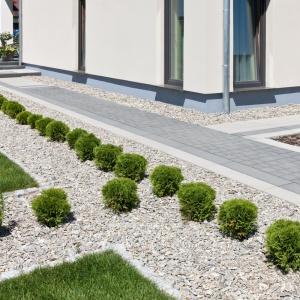 Betonowe kostki i płyty w stylu modern pomagają wytyczyć proste rzędy chodników lub ścieżek, tworzyć geometryczne płaszczyzny oddzielające roślinność. Na zdjęciu: kostka brukowa Perfect, Modern Line
