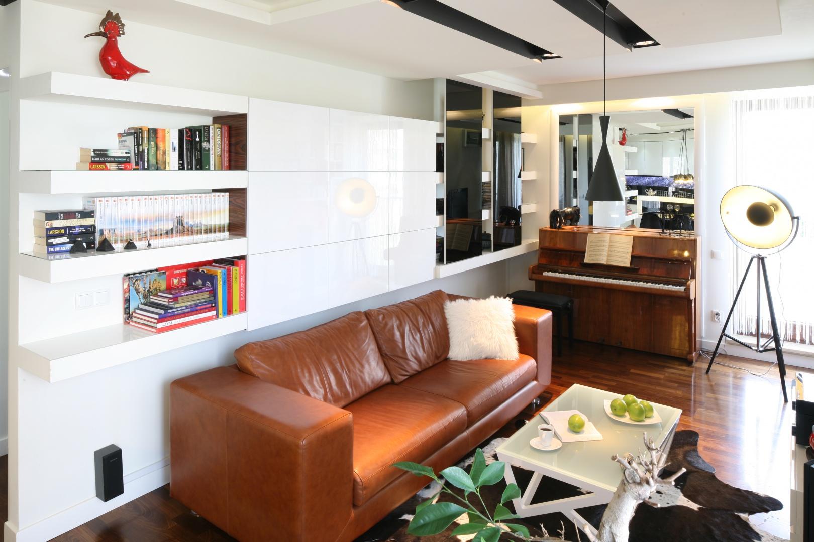 W tym wnętrzu miejsce na książki wygospodarowano nad kanapą. Część szafek jest otwarta, a część zamknięta. Projekt: Małgorzata Mazur. Fot. Bartosz Jarosz