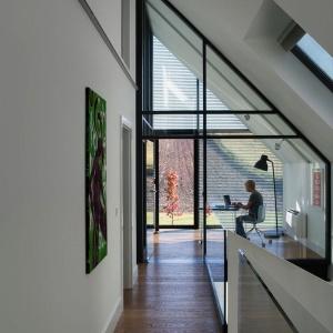Z gabinetu roztacza atrakcyjny widok na rozległy krajobraz, ale jest możliwy także wgląd w przestrzeń salonu i jadalni, znajdujących się poniżej – wszystko dzięki przeszkleniom zastępującym większość przegród w tym pomieszczeniu. Projekt: Ola Wołczyk. Fot. Hanna Długosz