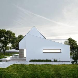 Biała nowoczesne w kształcie bryła domu została otoczona drewnianym tarasem. Fot. Genero