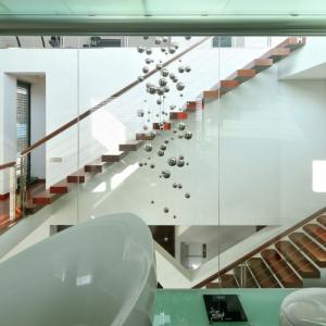 Nawet łazienka jest przeszklona, choć wrażenie to ma się tylko od wewnątrz, od środka zasłonić ją można praktycznymi żaluzjami. Na jej poziomie umieszczono fantastyczną dekorację w postaci ozdobnych srebrnych kuli, które wspaniale prezentują się na wysokiej na całość domu klatce schodowej. Fot. Tomasz Zakrzewski