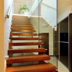 Drewniane schody ze szklaną balustradą prowadzą nas na piętro.
