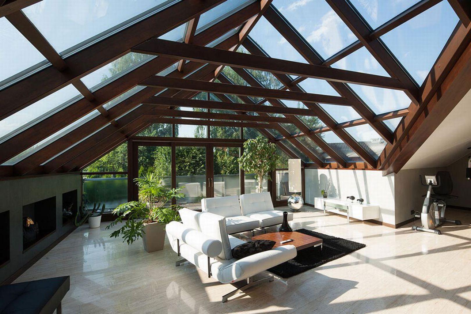 Jasne meble i kremowe płytki podłogowe doskonale prezentują się na tle ciemnej drewnianej konstrukcji dachu.