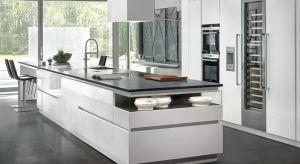 Minimalistyczny styl kuchni nadają geometryczne podziały i wyważone proporcje. Ponadczasową elegancję modelu podkreśla stonowana kolorystyka materiałów wykończeniowych. Fronty szaf i wyspy pokryte zostały błyszczącym białym lakierem, z który