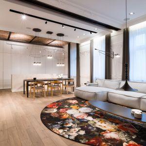 W części wypoczynkowej uwagę przyciąga bajecznie kolorowy dywan Moooi projektu Marcela Wandersa z realistycznymi motywami kwiatów oraz modułowa kanapa Le Noir polskiej marki Adriana Furniture w odcieniach szarości. Fot. Hamish Cox
