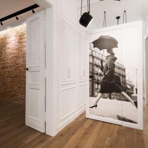 Wszystkie masywne drzwi z 1904 r. pozostały te same. Właściciele je odrestaurowali, pomalowali na biało i ozdobili nowoczesnymi czarnymi klamkami. Białe ściany i sufity zdobią misterne gipsowe sztukaterie. Do intymnej strefy mieszkania wchodzi się przez otoczone lustrem drzwi ukryte w ramie z wielką fotografią Richarda Avedona z 1957 r. Fot. Hamish Cox