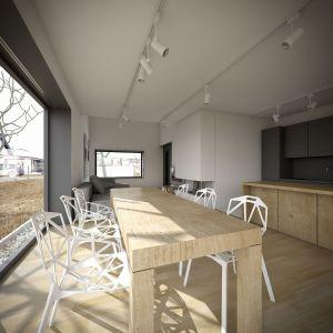 Strefa dzienna to połączenie części wypoczynkowej z kuchnią i jadalnią. We wnętrzu wyróżnia się ciekawe techniczne oświetlenie i geometryczne ażurowe krzesła. Fot. Kluj Architekci