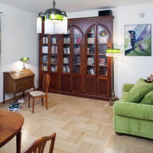 Zielona kanapa i zasłony w podobnym odcieniu pięknie komponują się z tradycyjnymi, ciemnobrązowymi meblami. Projekt: właściciele. Fot. Bartosz Jarosz