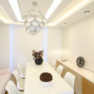 Poza eleganckim białym stołem oraz designerskimi krzesłami w jadalni znalazła się też pikowana sofka w kolorze pastelowego różu. Projekt: Agnieszka-Hajdas-Obajtek. Fot. Bartosz Jarosz