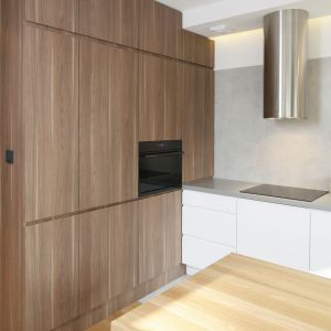 Czynnikiem ocieplającym rodzinną przestrzeń jest drewno: ciemny, brązowy fornir, z którego wykonano wysoką zabudowę. Projekt: Przemek Kuśmierek. Fot. Bartosz Jarosz