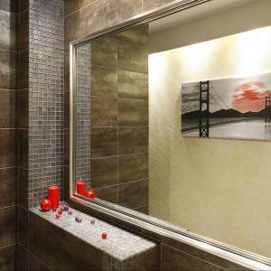 Metaliczny połysk jest obecny w całej łazience - nawet na ramie lustra. Projekt: Jolanta Kwilman. Fot. Bartosz Jarosz