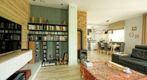 Projekt aranżacji wnętrza domu w Pile o pow.140 m2. Wnętrze zachowane w ciepłych odcieniach szarości z elementami drewna. Na szczególną uwagę zasługuje lustro w szerokiej drewnianej ramie które optycznie powiększa przedpokój. Naturalne zachowa