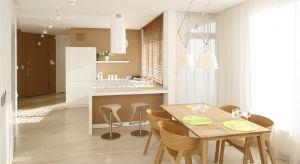 W tym nowoczesnym apartamencie kuchnia jest otwarta na salon, ale znajduje się na drugim planie. Jej kolorystyka – biel i jasny dąb – jest identyczna jak całej strefy dziennej.