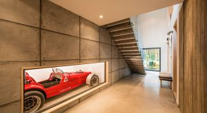 """Forma domu to dwie bryły ze spadzistym dachem oraz """"wbita"""" w nie asymetryczna kostka garażu. Uzupełniają go proste, surowe materiały – cegły, beton oraz blacha w odcieniach szarości.Całość stanowi współczesną interpretację tradycyjne"""