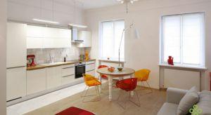 Biel nowoczesnego minimalistycznego salonu przełamana została pomarańczem i czerwienią. Mimo to głównymi atutami salonu nadal pozostaje jego niecodzienna wysokość (3,3m) i przestrzeń.