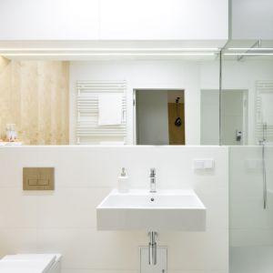 Biała łazienka z dekorem drewna stanowi spójną całość z reszta wnętrza. Fot. Stanisław Zajączkowski / Zajaczkowski Photography