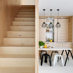 Minimalistyczna klatka schodowa jest elementem najbardziej przyciągającym wzrok w dwupoziomowym mieszkaniu. Stopnie oraz ściany pokryte są jednym materiałem (sklejką), tworząc drewnianą ramę odcinającą się w białej przestrzeni. Projekt pracownia 3XA. Fot. Stanisław Zajączkowski / Zajaczkowski Photography