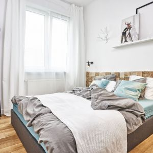 Drewno w nieoczywistej formie - ułożone na sztorc w połączeniu z białą farbą stanowi niezwykłą dekorację ściany za łóżkiem. Projekt: Katarzyna Kiełek, Agnieszka Komorowska-Różycka, Fot. Studio 17 Pixeli