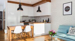 Mieszkanie na warszawskim Wilanowie prezentuje się bardzo przestronnie. Duże okna zapewniają odpowiednią ilość światła i optycznie powiększają pomieszczenie. Do zaaranżowania wnętrz użyto białej cegły na ścianach mieszkania.