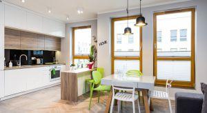 Mieszkanie w stylu nowoczesnym z mocnymi akcentami kolorystycznymi, w którym dominują szarości, biele oraz elementy drewniane.