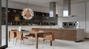 Jednolite powierzchnie wysokiej zabudowy są tłem dla wyspy, która w kompozycji kuchennej odgrywa główną rolę.