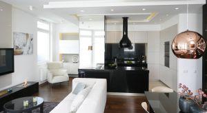 Kuchnia została zaaranżowana w stonowanej biało-czarno-beżowej kolorystyce. To oryginalne połączenie dodatkowo podkreślają duże lustrzane powierzchnie oraz dekoracyjne oświetlenie.