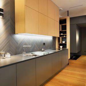 Geometryczne formy elementów dekoracyjnych, dwukolorowa jodełka na ścianie nad blatem w kuchni i satynowe fronty tworzą nowoczesne, eleganckie wnętrze. Projekt: GAO Arhitekti. Fot. Miran Kambic