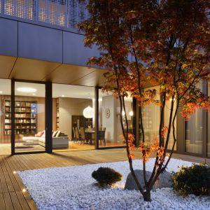 Dom w sercu Lublany, stolicy Słowenii. Międzynarodowym akcentem jest japoński ogród urządzony w atrium usytuowanym za panoramicznymi oknami salonu. Projekt: GAO Arhitekti. Fot. Miran Kambic