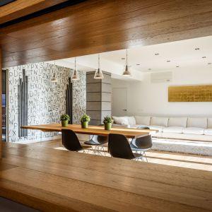 Naturalne materiały, jak drewno i kamień zestawiono z geometrycznymi formami. Oryginalnym akcentem są drobne, świetliste punkty zdobiące ściany przy wejściu do mieszkania – kryształy Swarovskiego. Projekt: Brain Factory – Architecture & Design. Fot. Marco Marotto