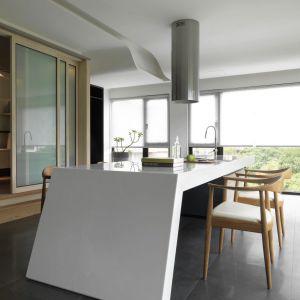 Obok nowoczesnych materiałów, takich jak Corian na wyspie kuchennej, dominują naturalne surowce, takie jak drewno i kamień oraz relaksująca paleta stonowanych barw. Projekt: JC Architecture. Fot. Kevin Wu