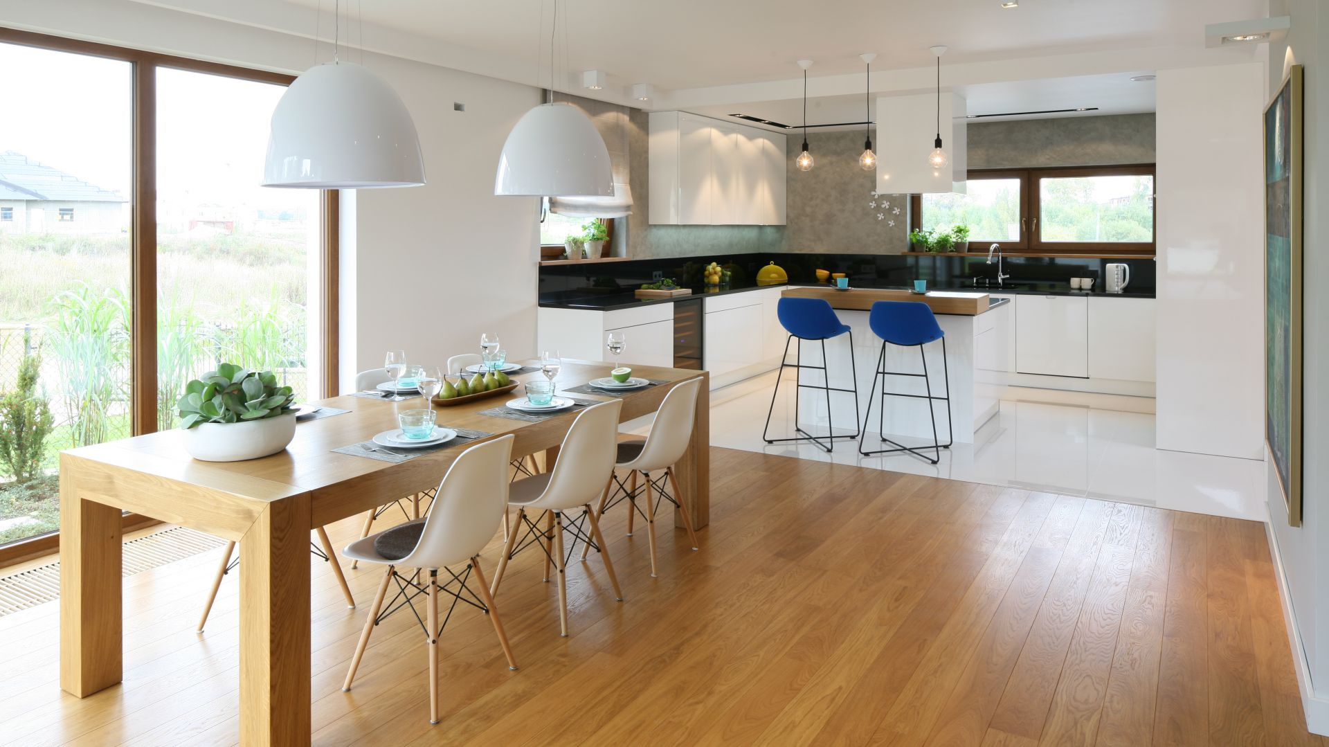 Długi drewniany stół sprawdzi się podczas rodzinnych przyjęć. Projekt: Małgorzata Galewska. Fot. Bartosz Jarosz