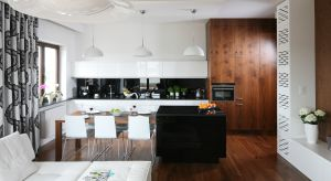 Białe kuchnie nie tracą na popularności. Oprócz aranżacji w stylu total look, mamy do wyboru również rozwiązanie cieplejsze i bardziej przytulne - to połączenie białych frontów z elementami drewna.