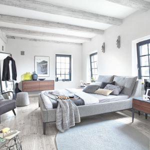 Drewno dopełnione elementami w kolorze szarym to modne i popularne rozwiązanie. Taka szafka dobrze komponuje się z tapicerowanym łóżkiem. Fot. Swarzędz Home